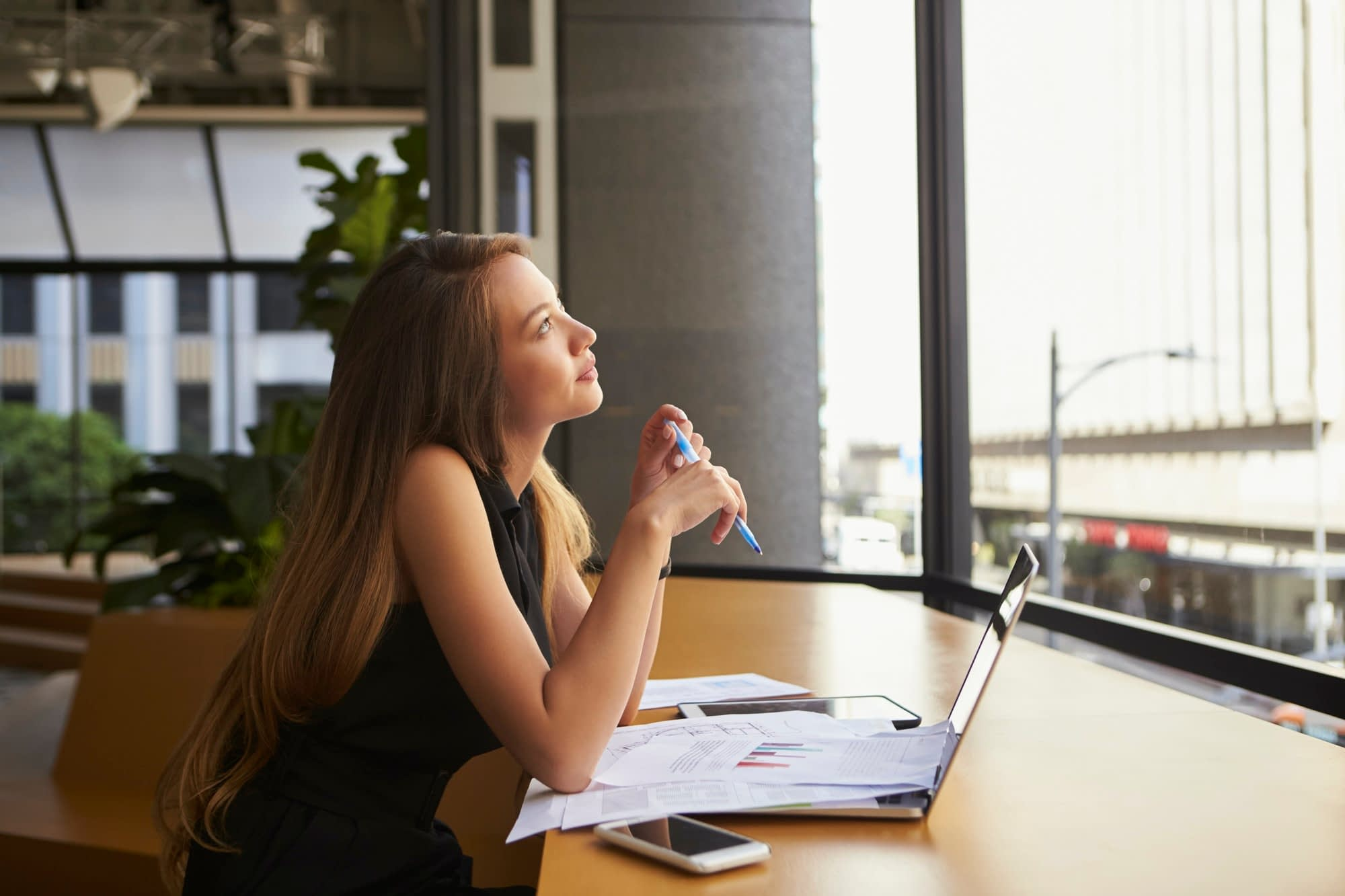 Businesswoman working in an office looking out of the window